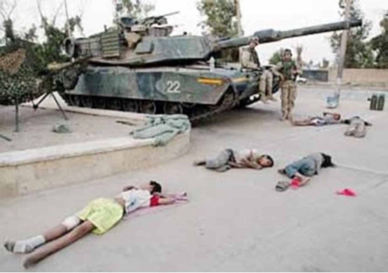 FALLUJAH, November 2004 — U.S. tank crew surveys bodies of children killed as U.S. tanks barreled into Fallujah. Many reported that tanks had rolled over wounded Iraqis lying in the streets, as U.S. forces advanced.